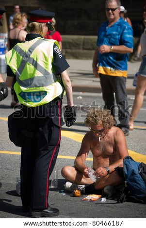 OTTAWA, CANADA - JULY 1: A female Police Officer confronts an unidentified, shirtless man on Wellington street during the July 1st, 2011 Canada Day celebrations in Ottawa, Ontario Canada.