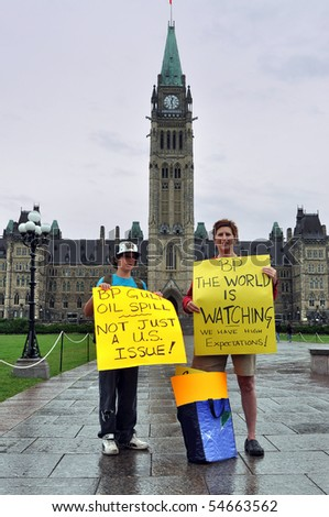 OTTAWA, CANADA - JUNE 6:  Two Canadians hold signs at demonstration on Parliament Hill imploring British Petroleum to do more to fix their oil spill disaster.  Ottawa, Ontario June 6, 2010.