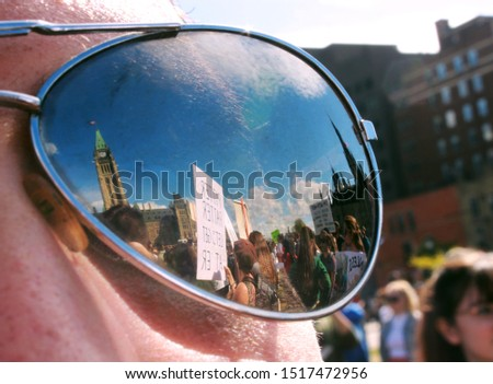 Ottawa, Canada - September 27, 2019 - The climate protest seen reflected in a pair of mirrored aviator sunglasses with Peace Tower #1517472956