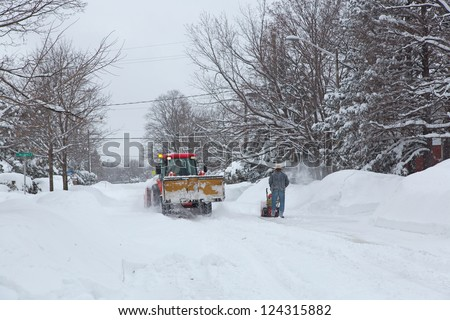 OTTAWA - DECEMBER 27: Unidentified workers clear snow December 27, 2012 in Ottawa, Ontario, Canada.  A major storm hit the area with over 20 cm of snow.