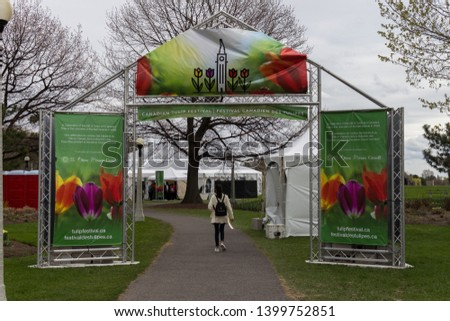 Ottawa, Ontario / Canada - May 13 2019: Young woman walking through the entrance gate poster sign for the Tulip Festival At Dow's Lake Commissioners Park