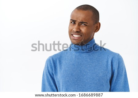 Ouch that hurts. Portrait of embarrassed and awkward young man cringe, grimacing and looking pity camera, feel discomfort trying to say something with caution, white background Stock photo ©