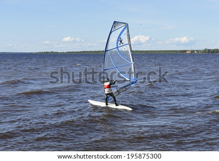 OULU, FINLAND - JULY 17, 2012:Windsurfing is surface water sport that combines elements of surfing and sailing. It consists of board usually 2 to 3 metres long, with volume of about 60 to 250 liters