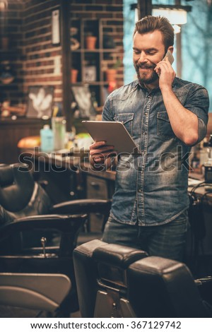 our appointment is on Monday! Cheerful young bearded man talking on mobile phone and looking at digital tablet while standing at barbershop