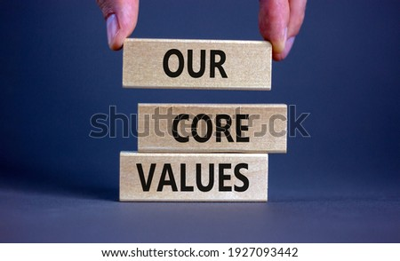 Our core values symbol. Concept words 'Our core values' on wooden blocks on a beautiful grey background, businessman hand. Business and our core values concept. Copy space.