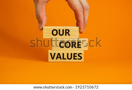 Our core values symbol. Concept words 'Our core values' on wooden blocks on a beautiful orange background, businessman hand. Business and our core values concept. Copy space.