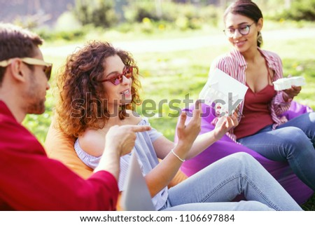 Our discussions. Alert curly-haired woman holding a house miniature and discussing work with her colleagues #1106697884