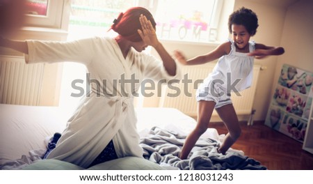 Our funny dance. African American mother and daughter playing on bed. Space for copy. close up.