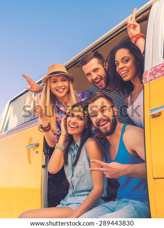 Our lives are full and happy. Group of happy young people smiling at camera and gesturing while sitting inside of retro mini van