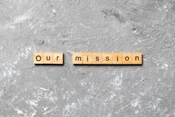 our mission on word written on wood block. our mission text on table, concept.