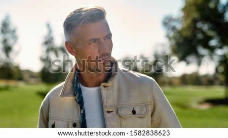 Our nature is wonderful. Portrait of handsome and stylish bearded man looking away while standing in the middle of the park. Nature concept. Beautiful people