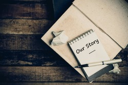 Our Story word on pages sketch book on wood table vertical