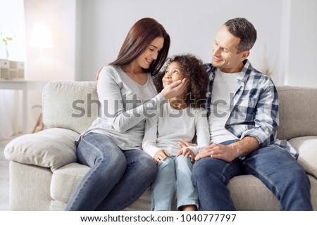 Our treasure. Attractive alert curly-haired girl smiling and sitting on the couch with her parents and they looking at her #1040777797