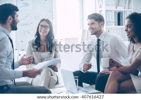 Our work is amazing! Young handsome man holding documents and discussing something with his coworkers with smile while sitting on the couch at office
