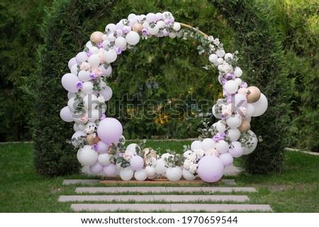 Ouside wedding ceremony. Balloon wedding arch in the garden. Wedding day.