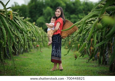 Out door portrait of young mother carries her baby in the farm  thailand.Traditional Thai dress.