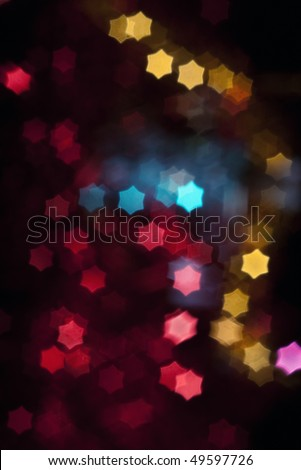 Out of focus and blurred colored star shape lights on black background