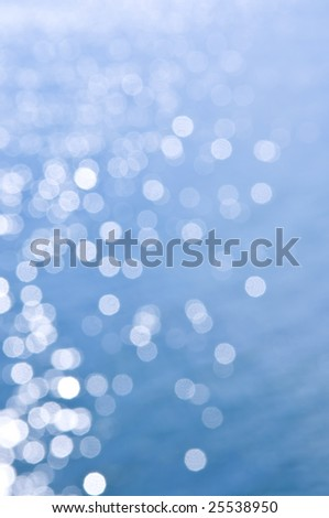 Out of focus bokeh background of blue water with sun reflections