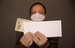 Out of focus caucasian man wearing face mask or N95 respirator holding a United States Treasury check representing economic impact payment as part of stimulus package due to  the COVID-19 coronavirus.