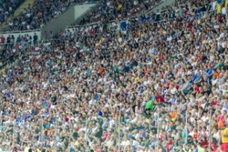 Out of focus, not sharp sport background - spectators at stadium. Crowds of fans in stands of football stadium during match Tribune with fans. Stands with football fans