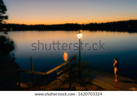 Out of focus photo. Blurred background. Panorama of calm water lake at sunset. Colorful skyline in orange and pink colors. A lonely woman stands on wooden pier going for swimming. Evening landscape.