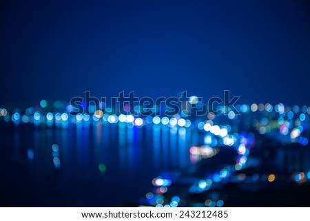 Out of focus sea bay and building in night time