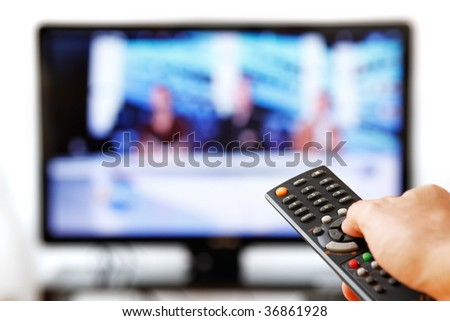 Out of focus TV LCD set and remote control in man\'s hand isolated over a white background.