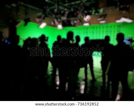 Out of focused and silhouetted people in green screen studio, behind the.scene of pre production of news broadcasting.