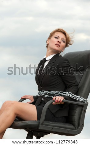 Out of office - working woman chained to her armchair