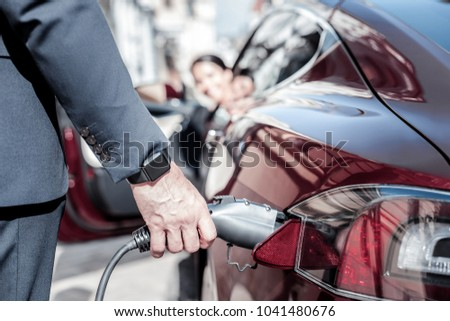 Out of petrol. Close up of a petrol nozzle being in use by a handsome nice confident businessman while standing near his car