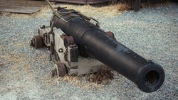 Out of service canon from the 18th century, chained to the ground and facing the camera. Military history concept.