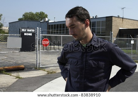 Out of work employee standing outside of factory