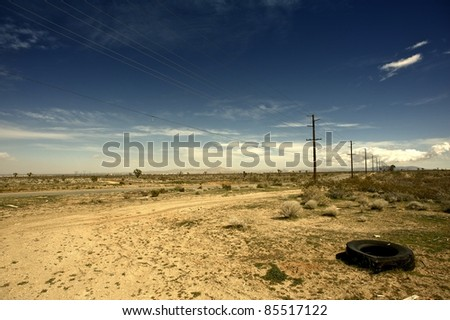 Outback California USA - California Suburbs Desert Landscape with Old Broken Tire on the Road Side.