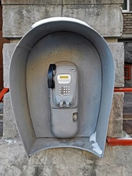 Outdated city payphone hangs on the rough wall of old building
