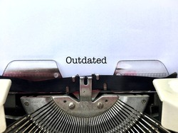 OUTDATED, word title heading typewritten in black on white paper on vintage manual typewriter machine, suitable concept for obsolete technology, business, ideas, policies, objects