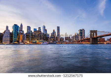 Outdooors view on NYC New York City Brooklyn Bridge Park by east river, cityscape skyline at sunset, dusk, twilight, blue hour, dark night, skyscrapers, buildings, waves, blurred, blur, blurry boat