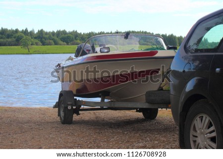 Outdoor activities, boat launch - descent of a white-red motor plastic boat on a trailer with a car on the water on a sandy slipway on the background of the river and the shore with green trees #1126708928