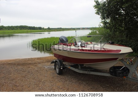 Outdoor activities - descent of a white-red motor plastic boat on a trailer with a car on the water on a sandy slipway on the background of the river and the shore with green trees #1126708958