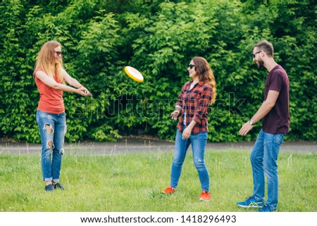 outdoor activities. Lifestyle. Full length of young people in casual wear playing while spending carefree time outdoors. frisbee.