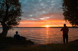 Outdoor activities. Silhouette of a fisherman and his friend on the lake at sunset. Man resting on the shore, fisherman catching fish. Sunset landscape