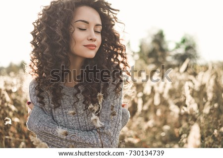Outdoor atmospheric lifestyle photo of young beautiful lady. Brown hair and eyes. Warm fall. Autumn vibes. Softness, warmth and comfort