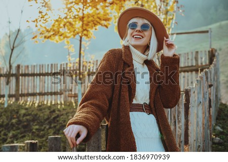 Outdoor autumn fashion, lifestyle portrait of smiling woman, model wearing trendy outfit with hat, sunglasses, faux fur coat, knitted sweater, wicker belt, posing on nature. Copy, empty space for text Photo stock ©