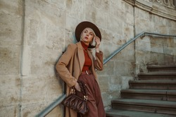 Outdoor autumn fashion portrait of elegant, luxury woman wearing trendy midi beige, camel color coat, brown hat, trousers, orange turtleneck, holding leather pouch bag, posing in street of city