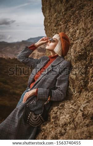 Outdoor autumn fashion portrait of young elegant blonde model, girl wearing beret, orange turtleneck, long checkered coat, sunglasses, holding trendy small bag, handbag, handbag, posing in mountains