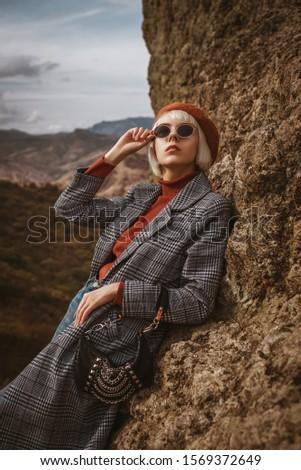 Outdoor autumn fashion portrait of young elegant blonde model, woman wearing beret, orange turtleneck, long checkered coat, sunglasses, holding trendy small bag, handbag, handbag, posing in mountains