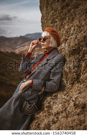 Outdoor autumn fashion portrait of young elegant model, lady wearing beret, orange turtleneck, long checkered coat, dark sunglasses, holding trendy small bag, handbag, handbag, posing in mountains