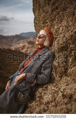 Outdoor autumn fashion portrait of young elegant model, woman wearing beret, orange turtleneck, long checkered coat, dark sunglasses, holding trendy small bag, handbag, handbag, posing in mountains