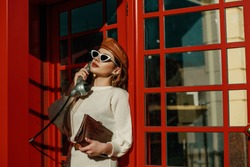 Outdoor autumn fashion portrait of young elegant woman wearing stylish  beret, sunglasses, white sweater, holding brown textured crocodile leather handbag, posing in red call box. Copy, empty space