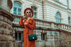 Outdoor autumn portrait of elegant woman wearing long orange trench coat, hat, sunglasses, with green croco textured bag, posing in street of European city. Copy, empty space for text