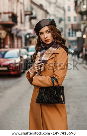 Outdoor autumn portrait of young elegant fashionable lady wearing trendy beret, camel color coat, plaid scarf, holding textured reptile faux leather baguette handbag, posing in street of European city